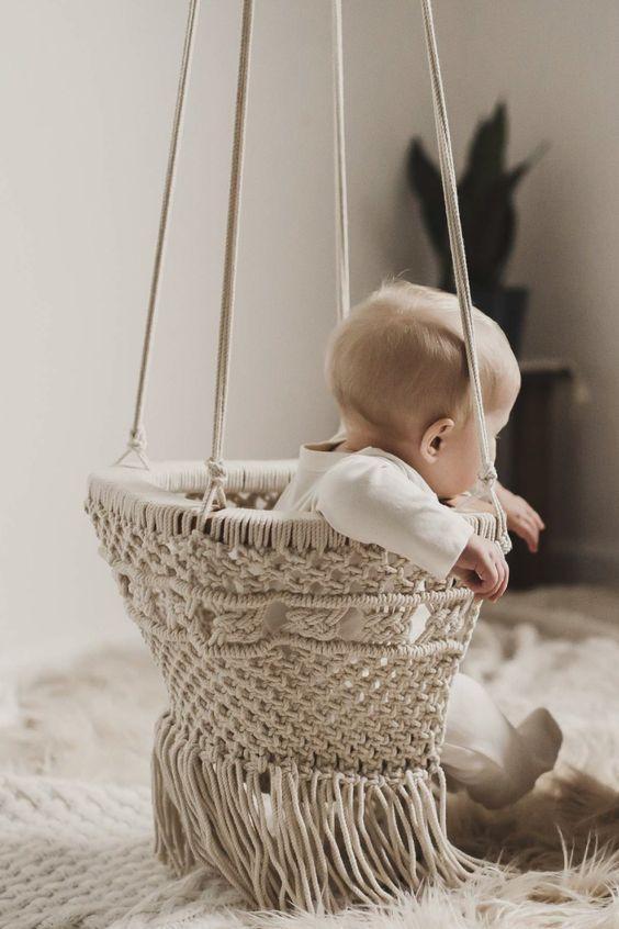 Macramê em formato de cadeirinha de bebê.