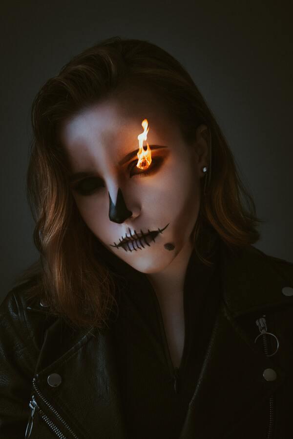 Foto de uma mulher branca com maquiagem de espantalho e com o olho pegando fogo.