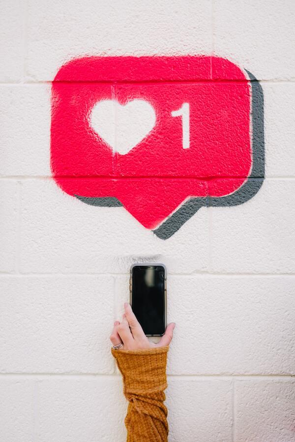 """parede com o grafite do símbolo """"like"""" do instagram e uma mão segurando um celular"""