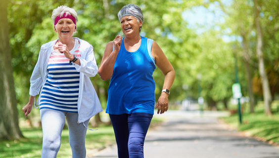 Two older women walking in a park for exercise