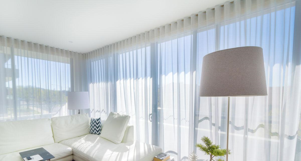 sheer curtains next to white couches