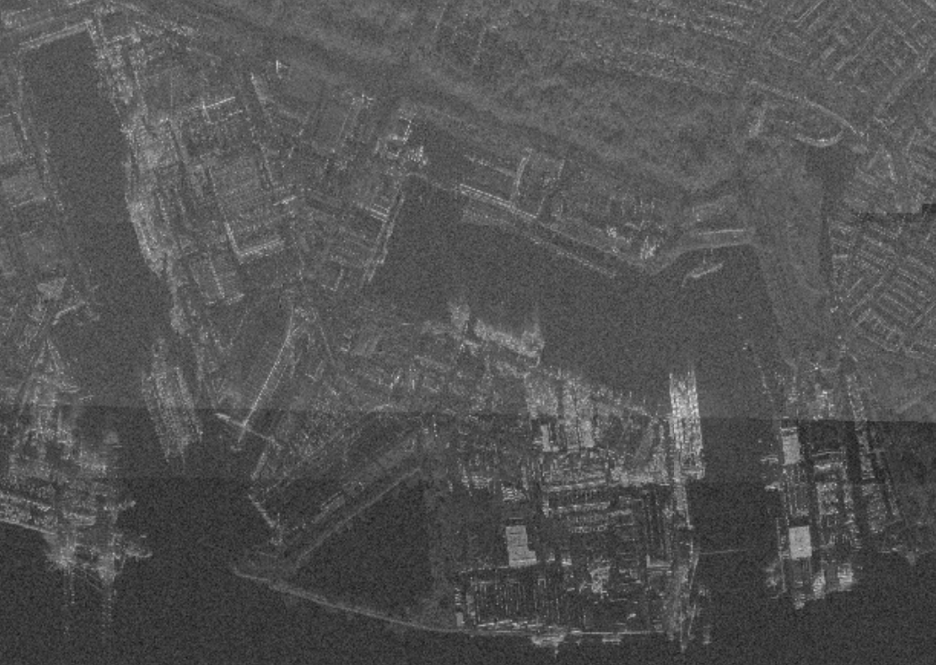 A grainy black and white view of a waterfront.