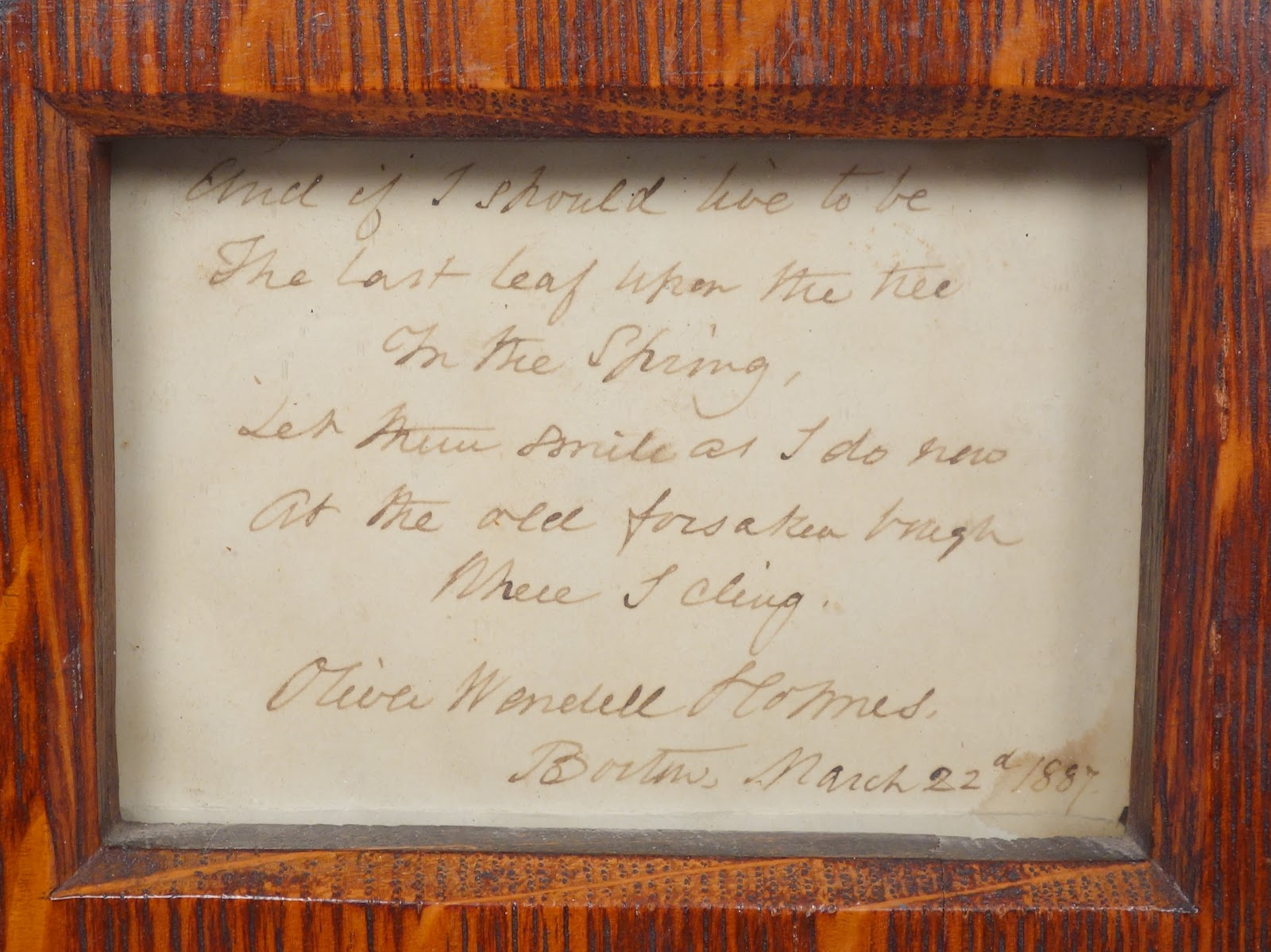 handwriting on paper in a wooden frame