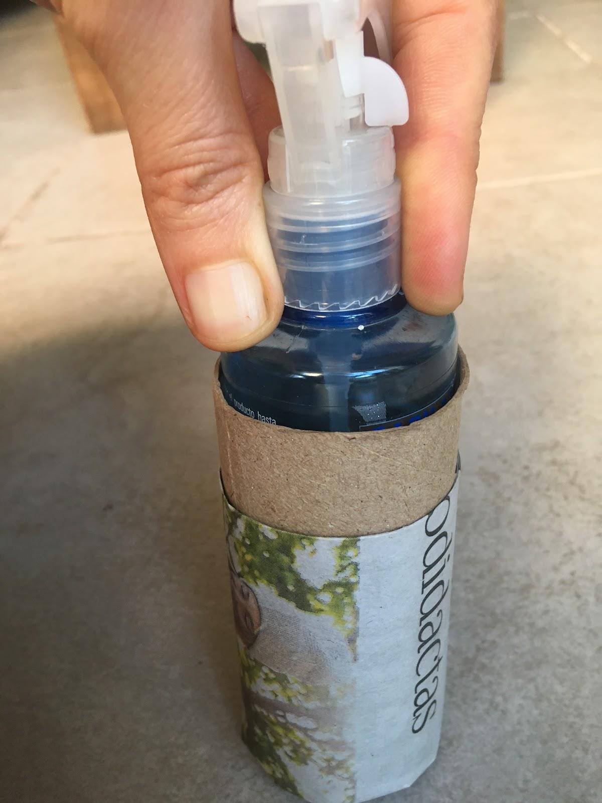 el pulverizador colocado dentro del rollo de cartón recientemente cubierto en papel de diario.
