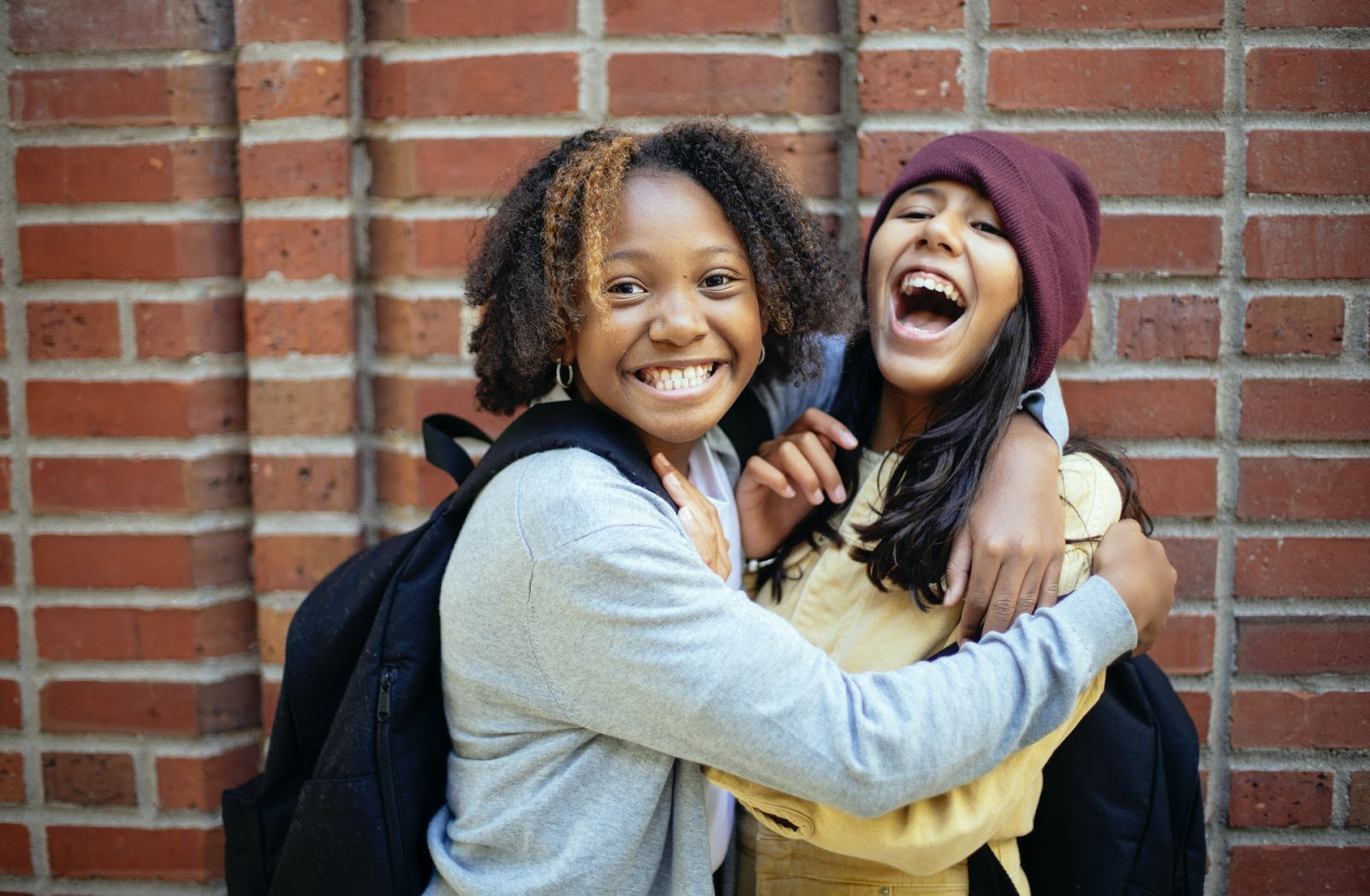 Two young girls of color hug and laugh while wearing backpacks with a red brick backdrop.