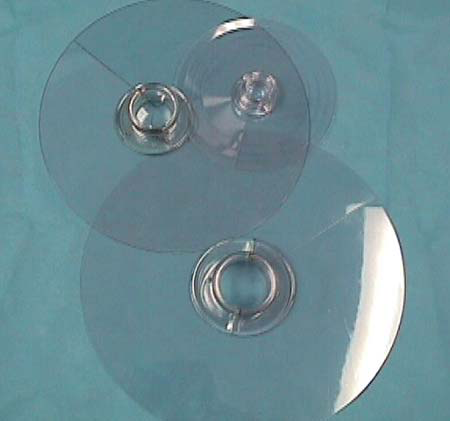 Plastic circular disks use a plastic clamshell shape to envelop the neck