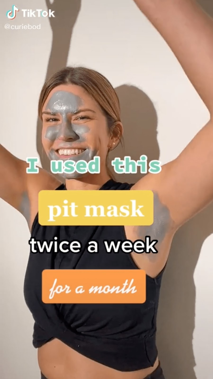 """Screenshot of Curie's tiktok which features a woman standing with her arms in the air with text that says """"I used this pit mask twice a week for a month."""""""