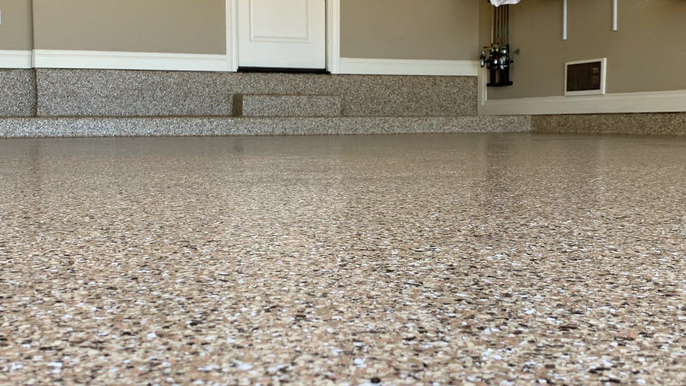 A up close photo of a garage floor coated with small flakes of beige, black, and white to look rock-like.