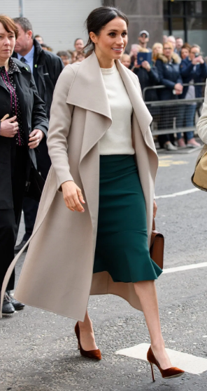 Meghan Markle in formal knee-length skirt, top, and an ankle-length coat