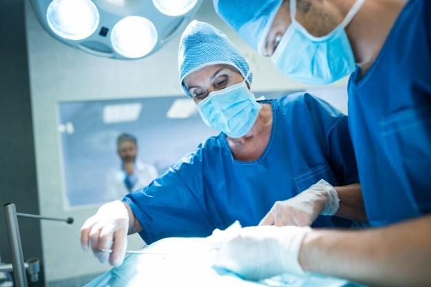 Surgeons performing operation in operation room