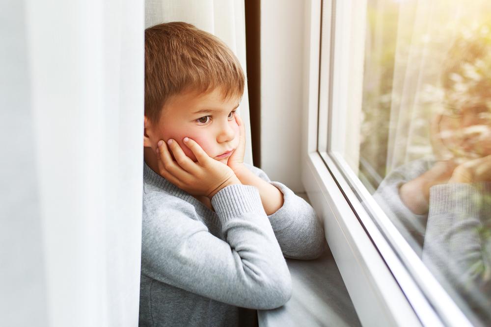 criança olhando pela janela