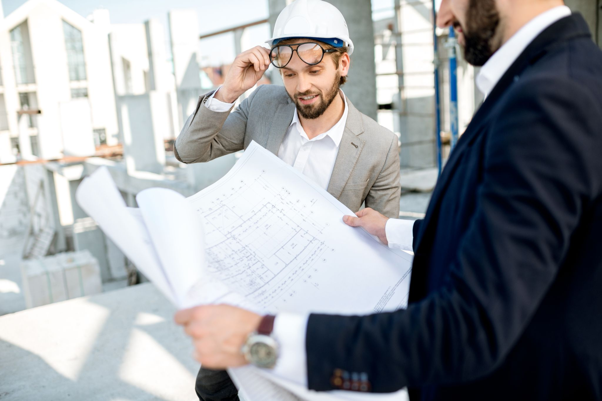 Two structural engineers wearing hard hats and looking over blueprints.
