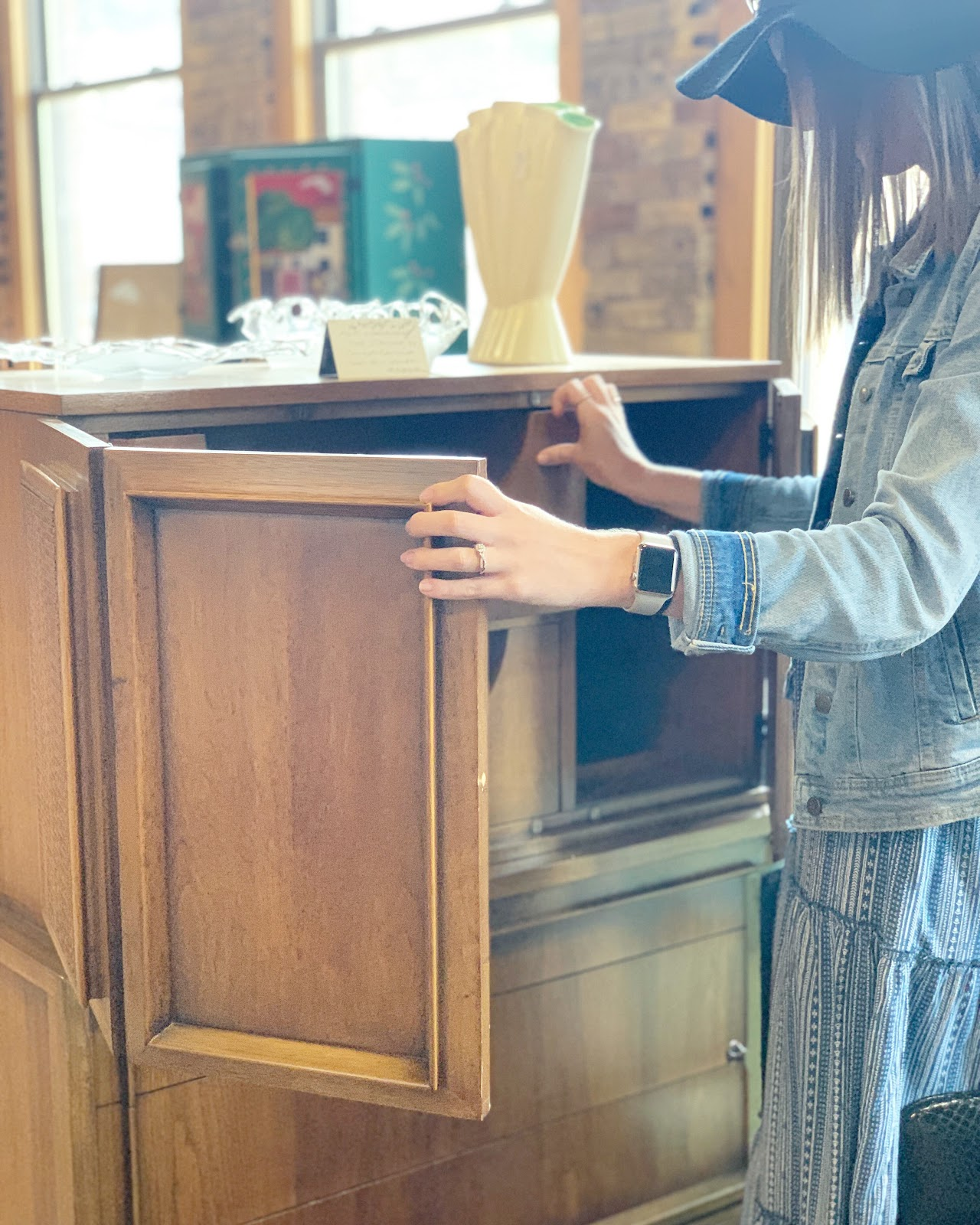 Woman looking for eco-friendly furniture at a second hand store.
