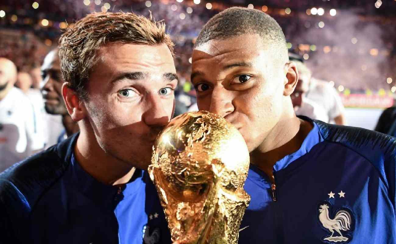 Alt: Antoine Griezmann and Kylian Mbappé of France kiss the World Cup Trophy - Photo credit FRANCK FIFE/AFP via Getty Images