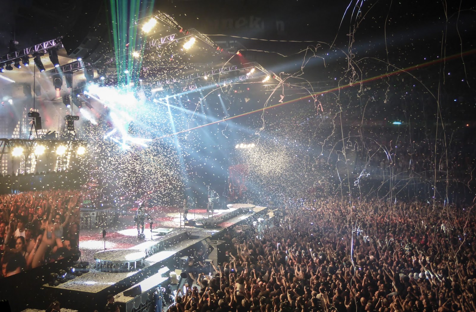 A picture of a music concert with musicians on stage and fans downstage: Going On Tour