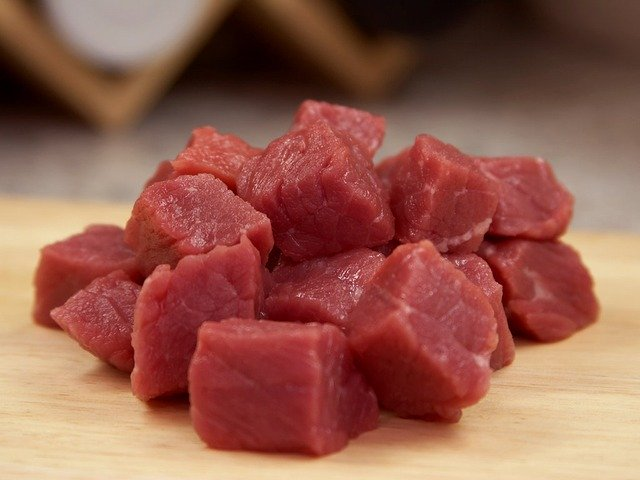 A small pile of cubes of raw meat on a cutting board.