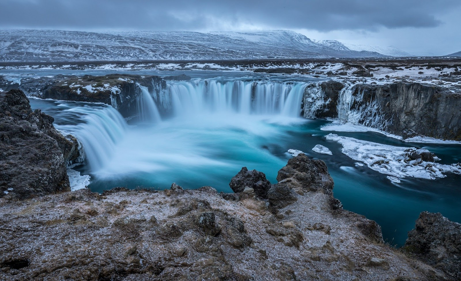 godafoss wide short waterfall ice and snow covered in winter iceland