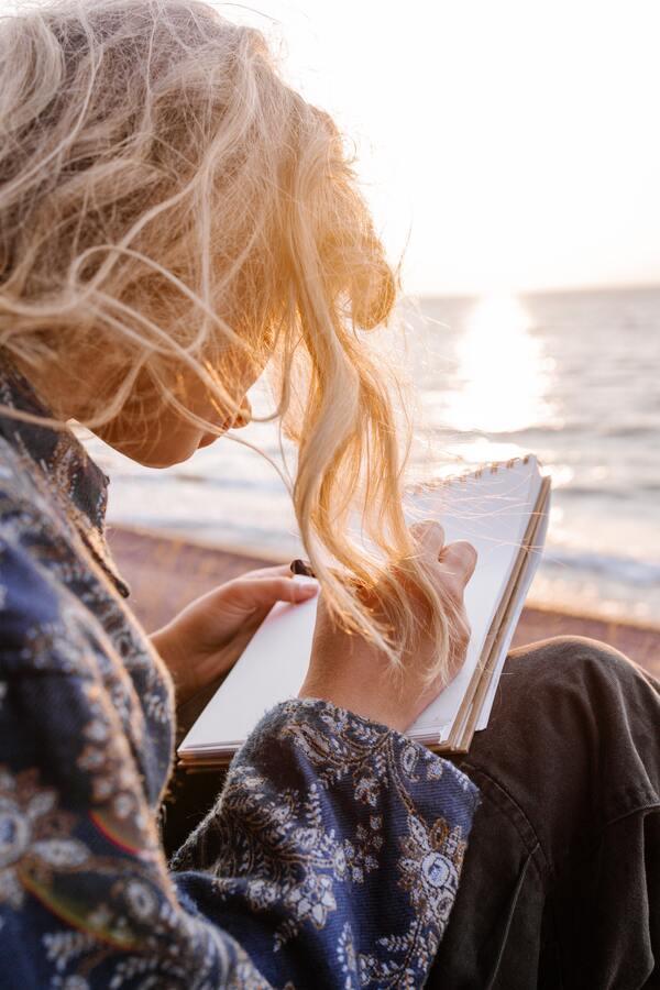 Mulher sentada na areia escrevendo em um caderno