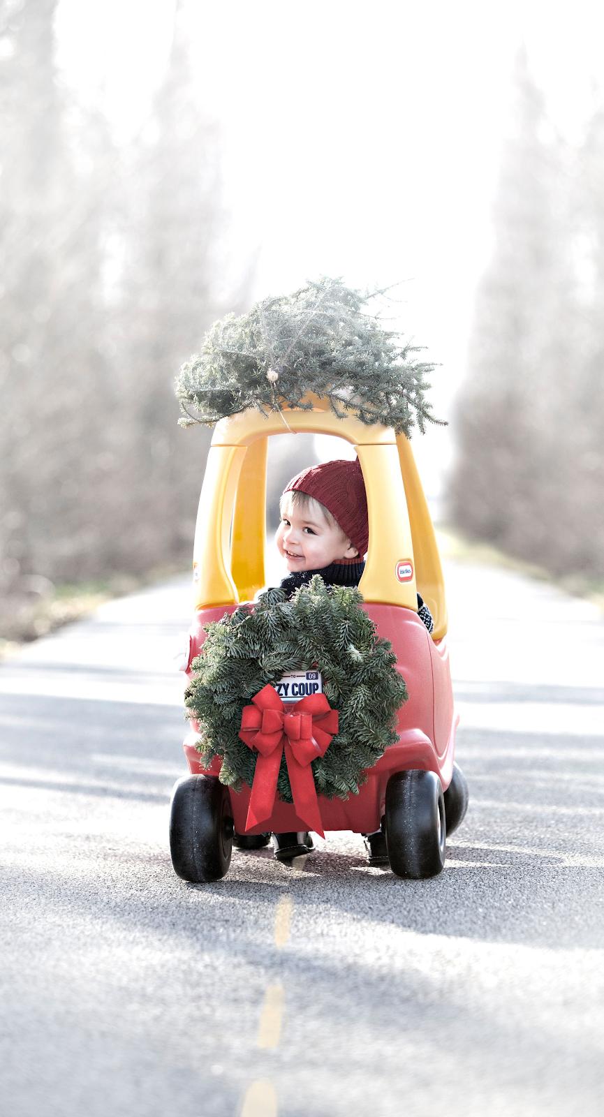 fun christmas card pose of toddler in little tikes coupe with a wreath and happy holidays clothes