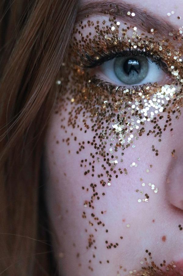 foto do olho verde de uma mulher com glitter em volta do olho
