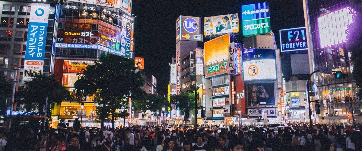 crowded street at night in Japan with multiple digital billboards lighting up the area