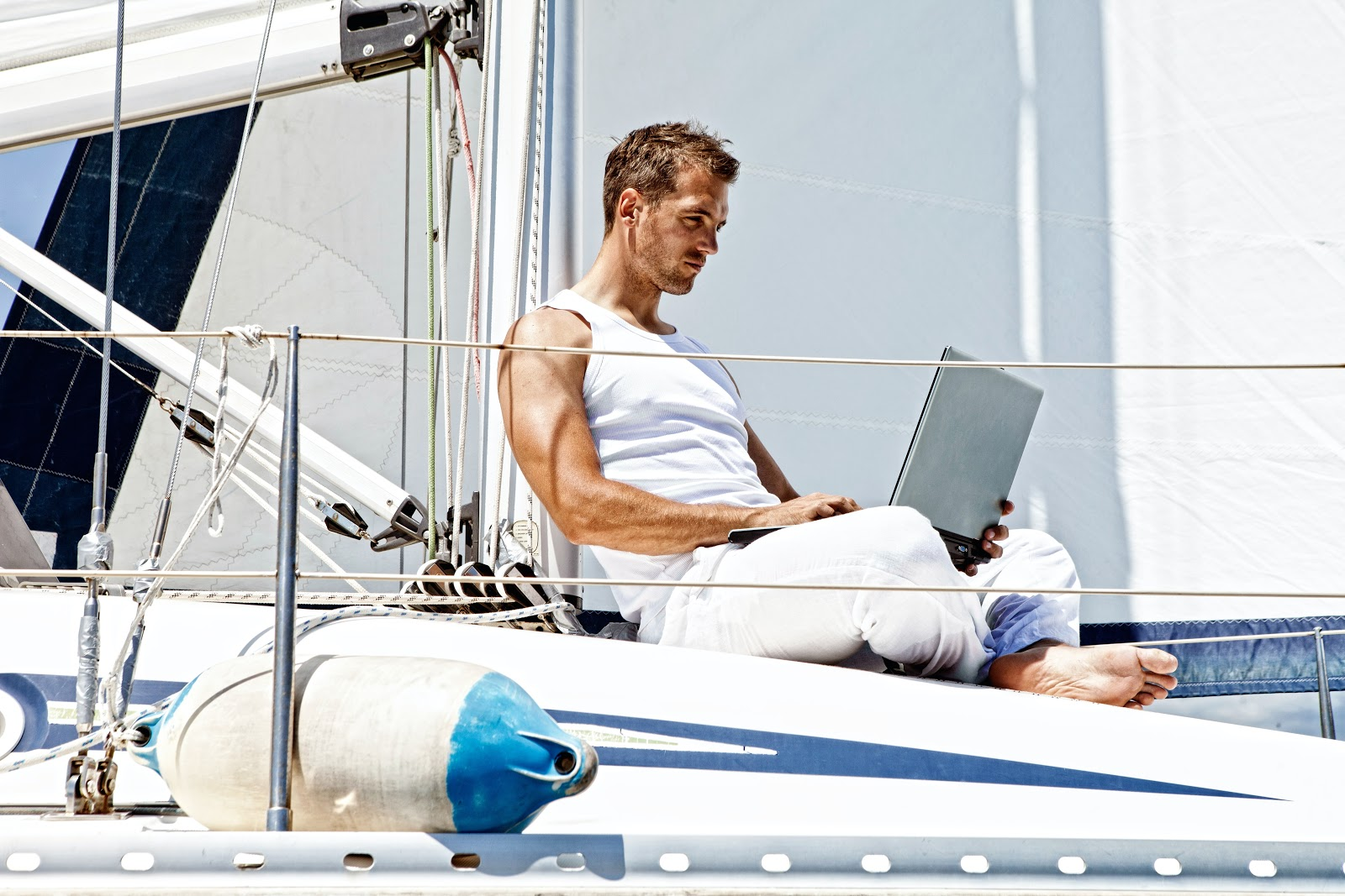 A man on the computer on a boat.