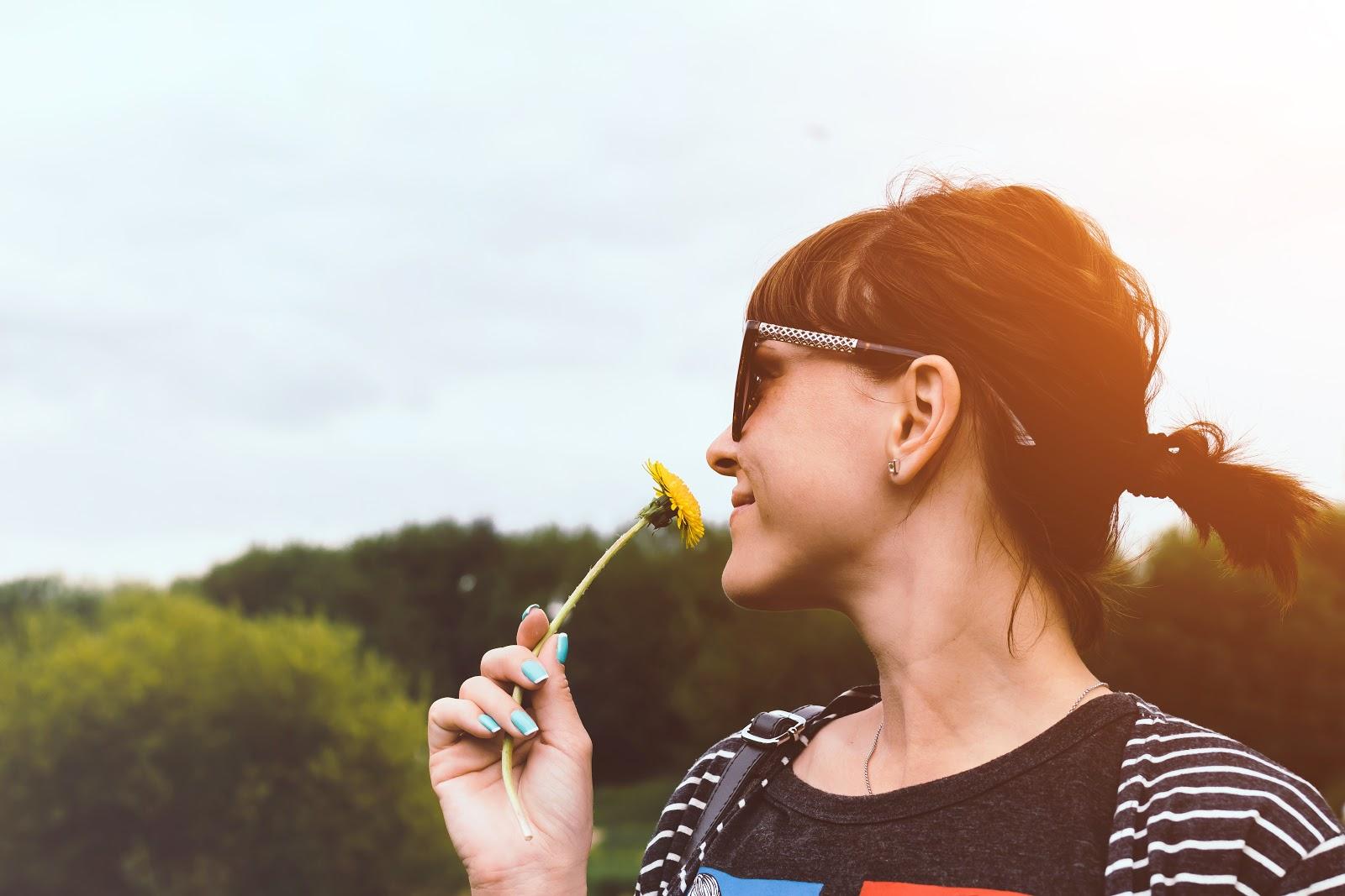 Autoimmune diet: A woman smells a flower