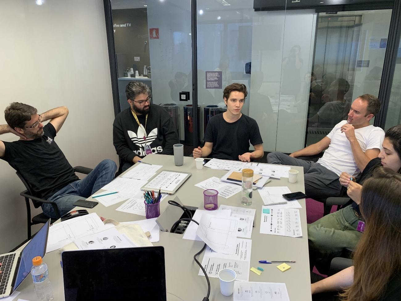 Six people sitting around a table filled with pieces of paper