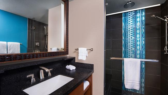 Bathroom with granite style counter, sink, mirror and towel rack, next to shower with decorative back splash