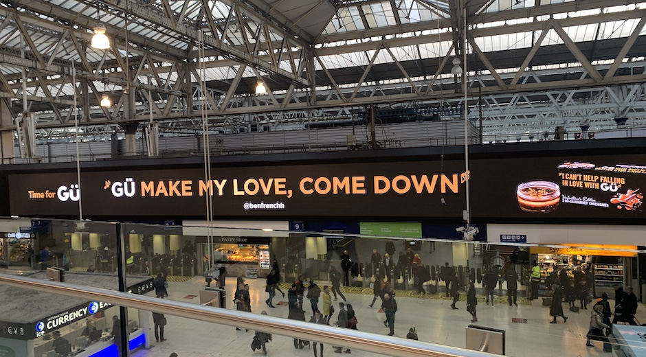 """Gü's text on a digital billboard in UK's station, saying, """"Gü make my love, come down"""""""