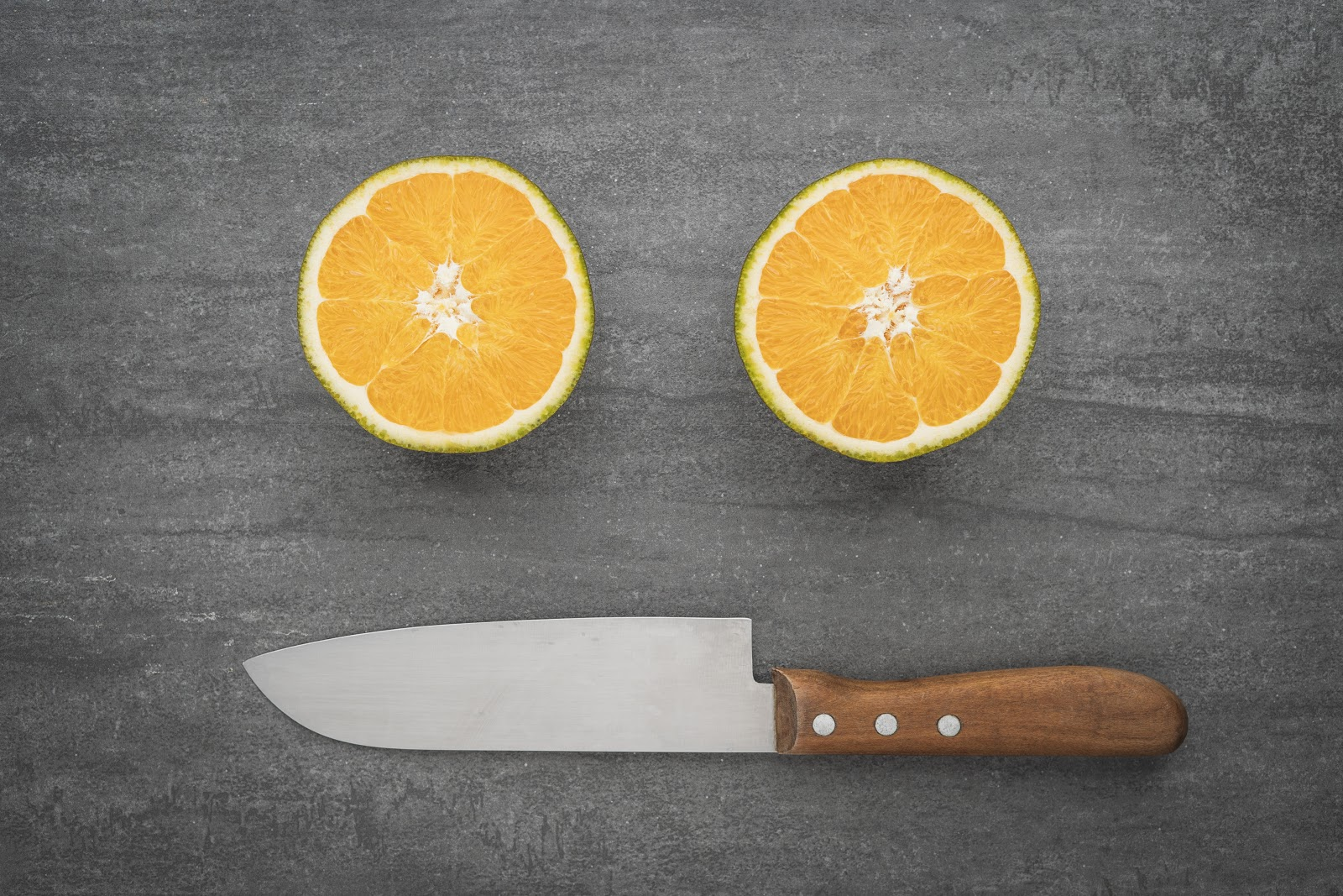 Two halves of an orange lay cut-face up on a table with a knife.