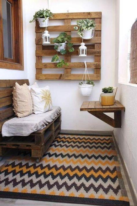 Varanda em estilo rústico com tapete cinza, branco e amarelo, sofá de pallet com estofado branco e almofadas, mesinha de madeira e jardim vertical