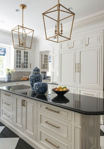 traditional black and white kitchen with handcrafted white cabinets, brass hardware, and large center island with black countertop