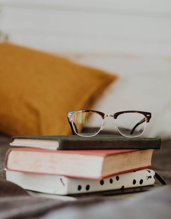 foto de três livros com um óculos de grau em cima