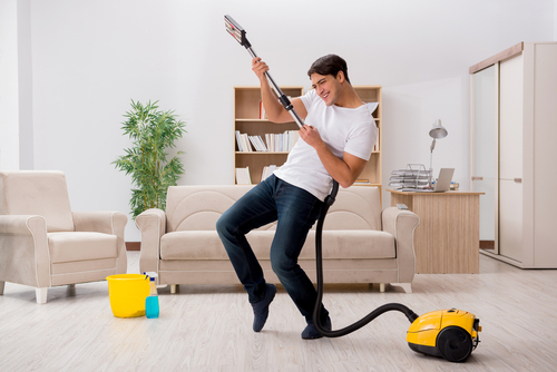 A guy using a vacuum like a guitar - doing air guitar with the hose/attachements in an apartment living room.