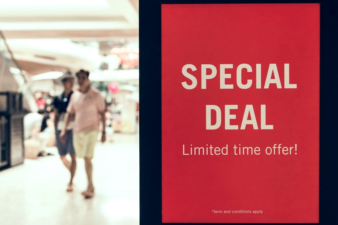A sign in a store saying SPECIAL DEAL with people in the background.