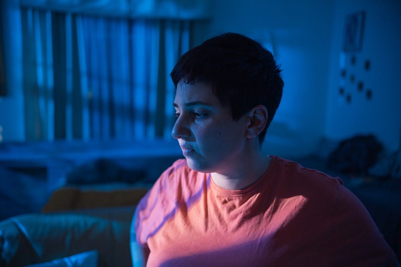 A portrait of the lead actor in a dark blue lit room wearing a reddish t-shirt. She is looking down
