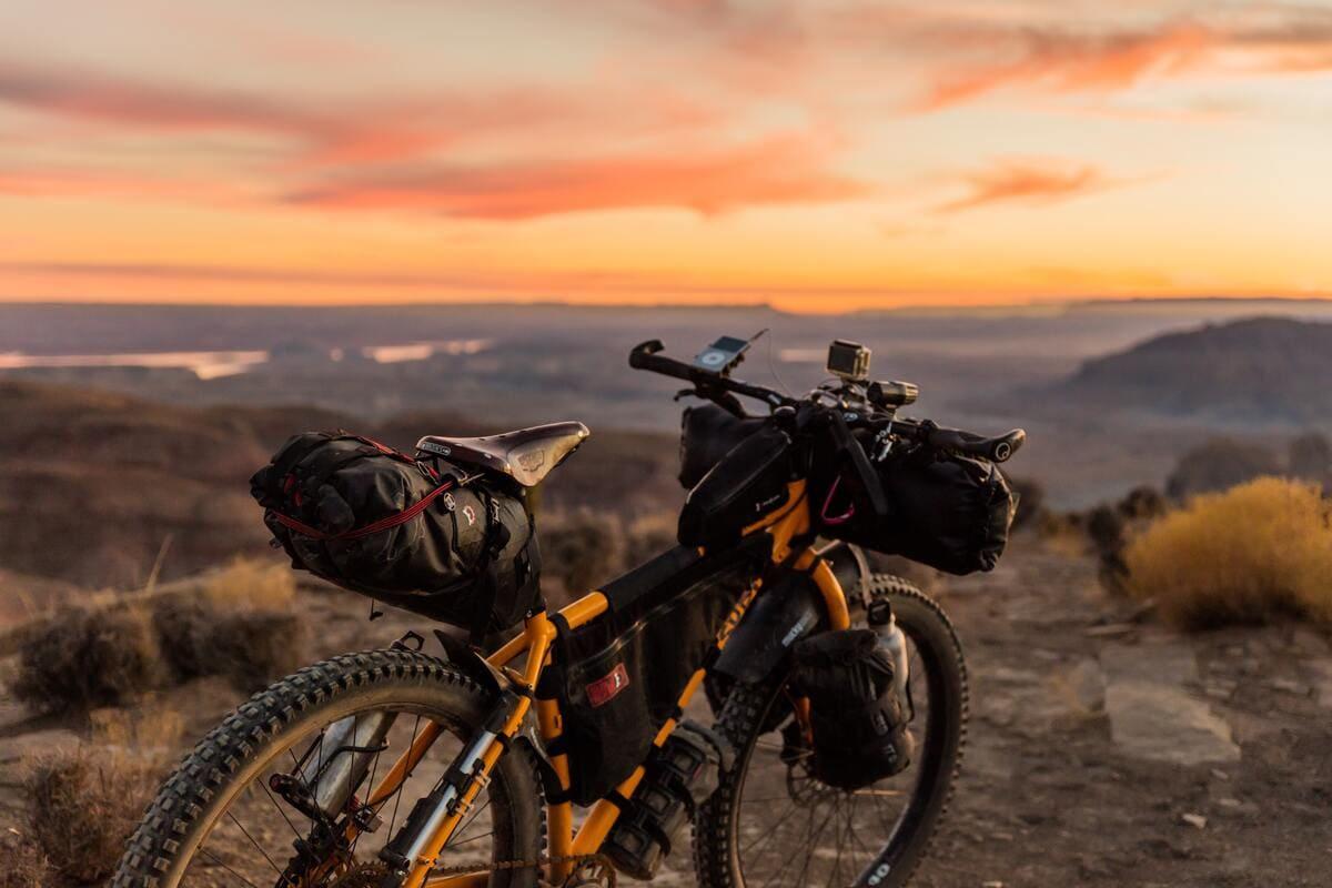Una bicicletta con alcune borse legate al telaio in un paesaggio al tramonto