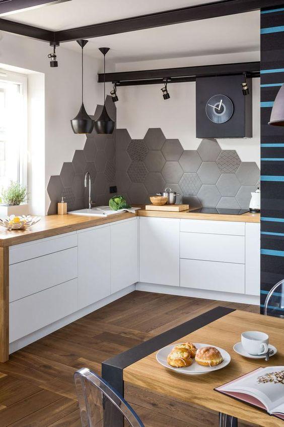 Cozinha com armário branco e bancada amadeirada, piso e mesa de madeira com cadeira acrílica transparente, parede da pia com azulejo hexagonal cinza em meia parede, demais pintada de branca e luminárias pendentes pretas.
