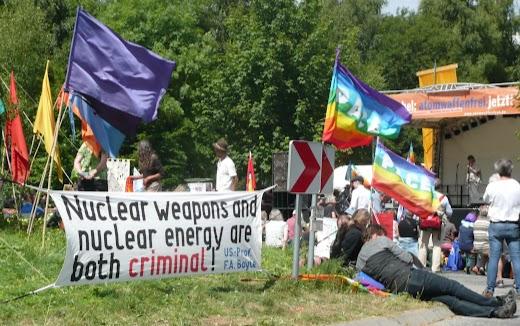 Lagernde Atomgegner mit bunten Fahnen und Transparenten: »Nuclear weapons and nuclear energy are both criminal!« und im Hintergrund an der Bühne »Büchel: atomwaffenfrei. jetzt!«.