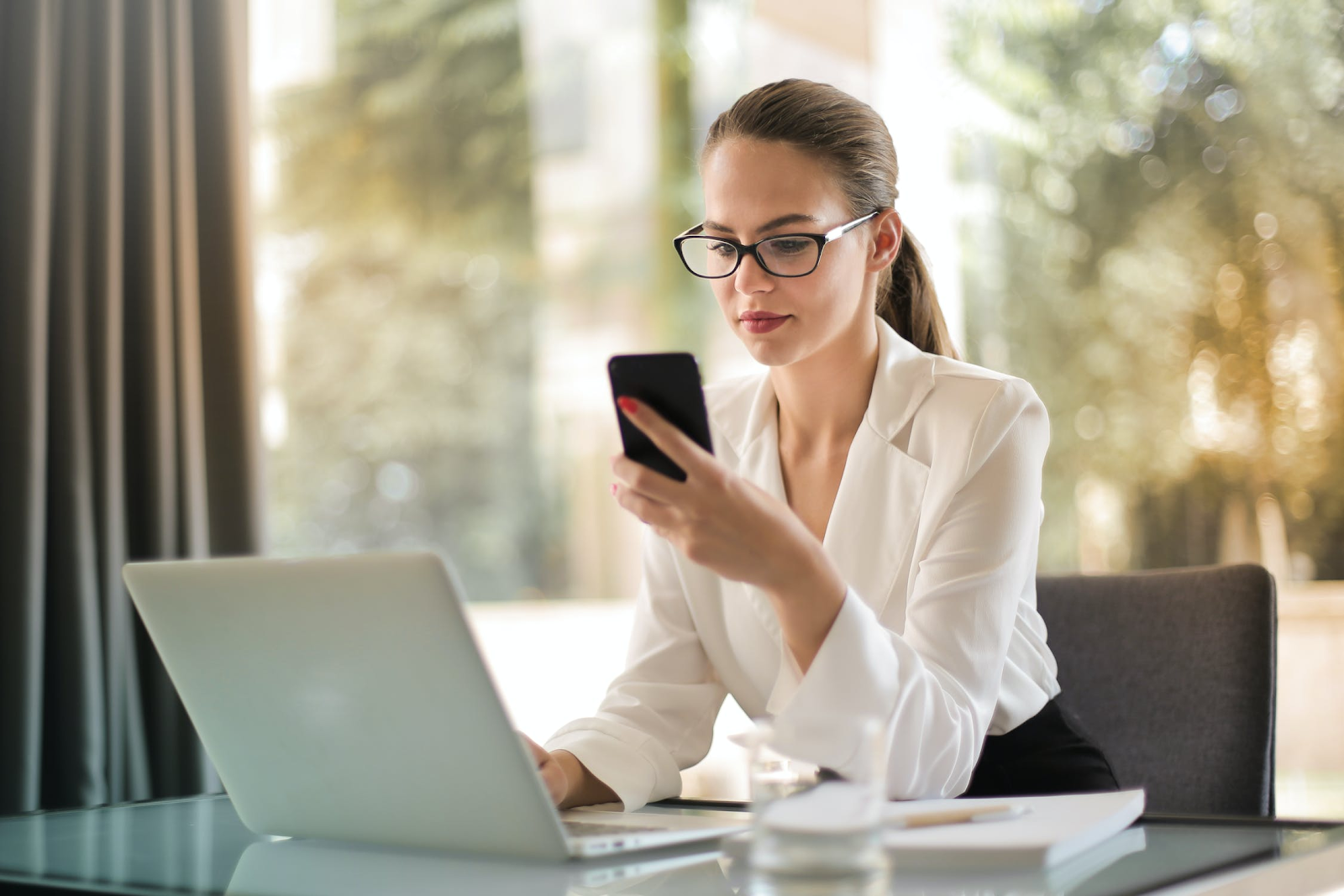 Woman wearing glasses checking her phone while working on her laptop