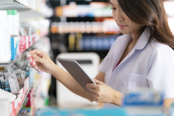 woman looking at tablet while at a pharmacy