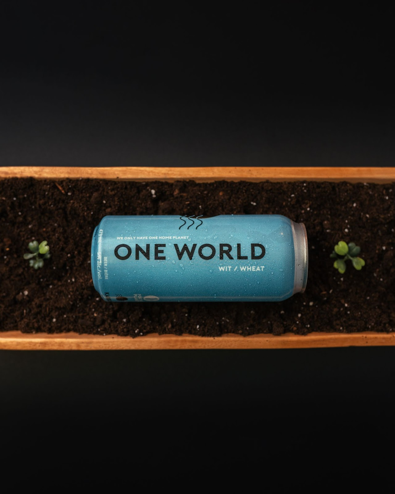 A Can of One World Wit laying on its side in a planter.  The can is turqouise and has the name of the beer down the side.