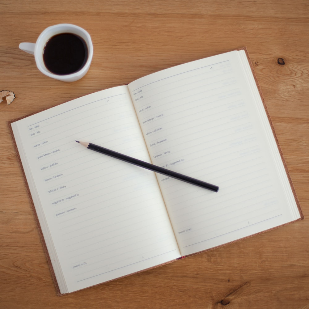 An overhead shot of a pencil on an open planner next to a cup of coffee