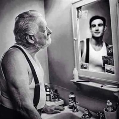 Um senhor mais velho observando o próprio reflexo no espelho enquanto um rapaz jovem expressando o desejo de retornar à juventude