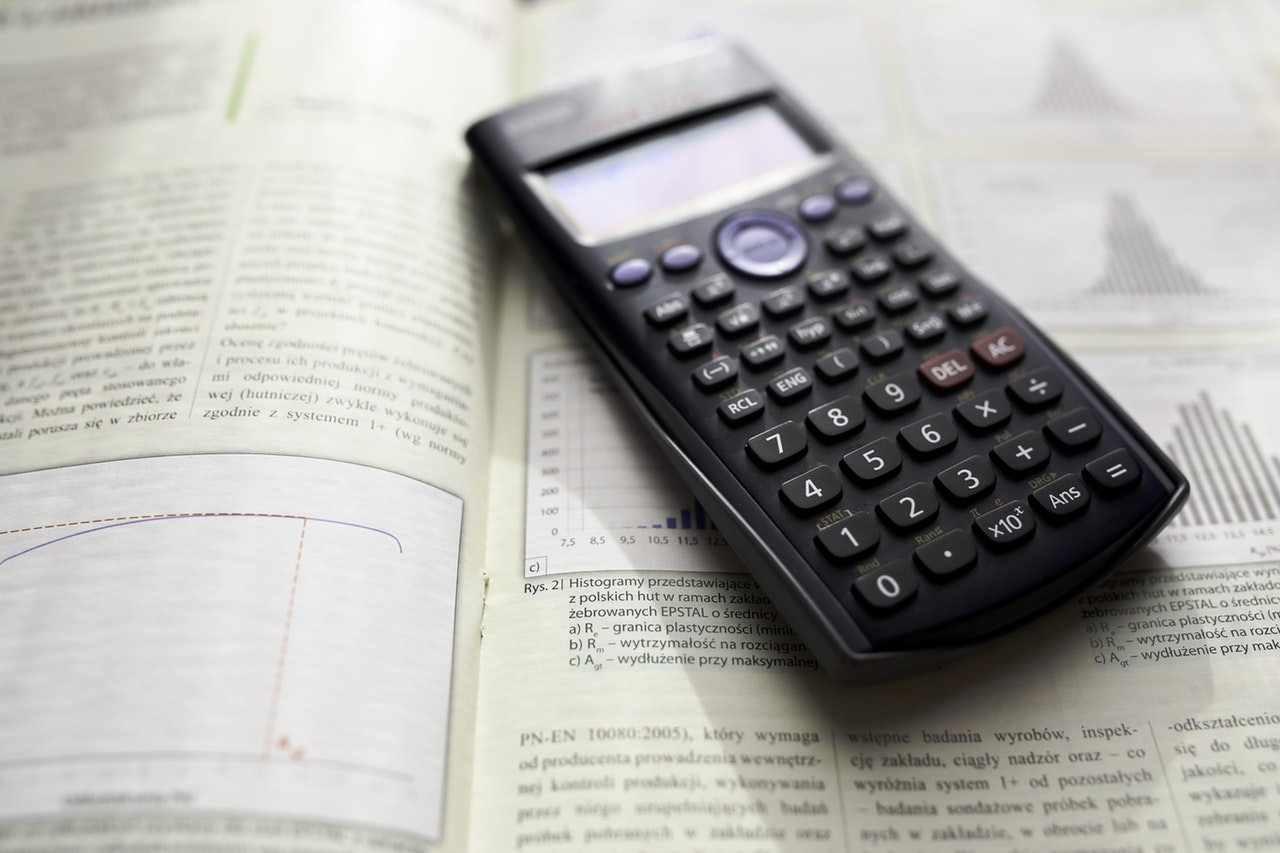A photograph of a scientific calculator sitting on an open math textbook.