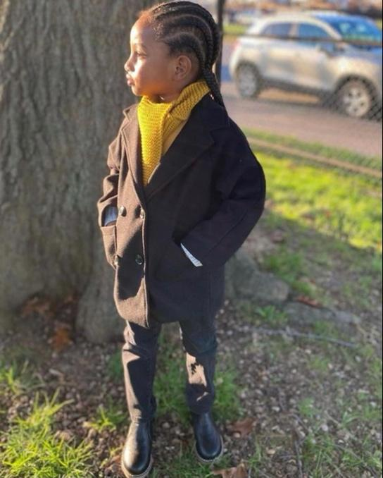 A person wearing a black coat and yellow scarf standing next to a tree  Description automatically generated with medium confidence