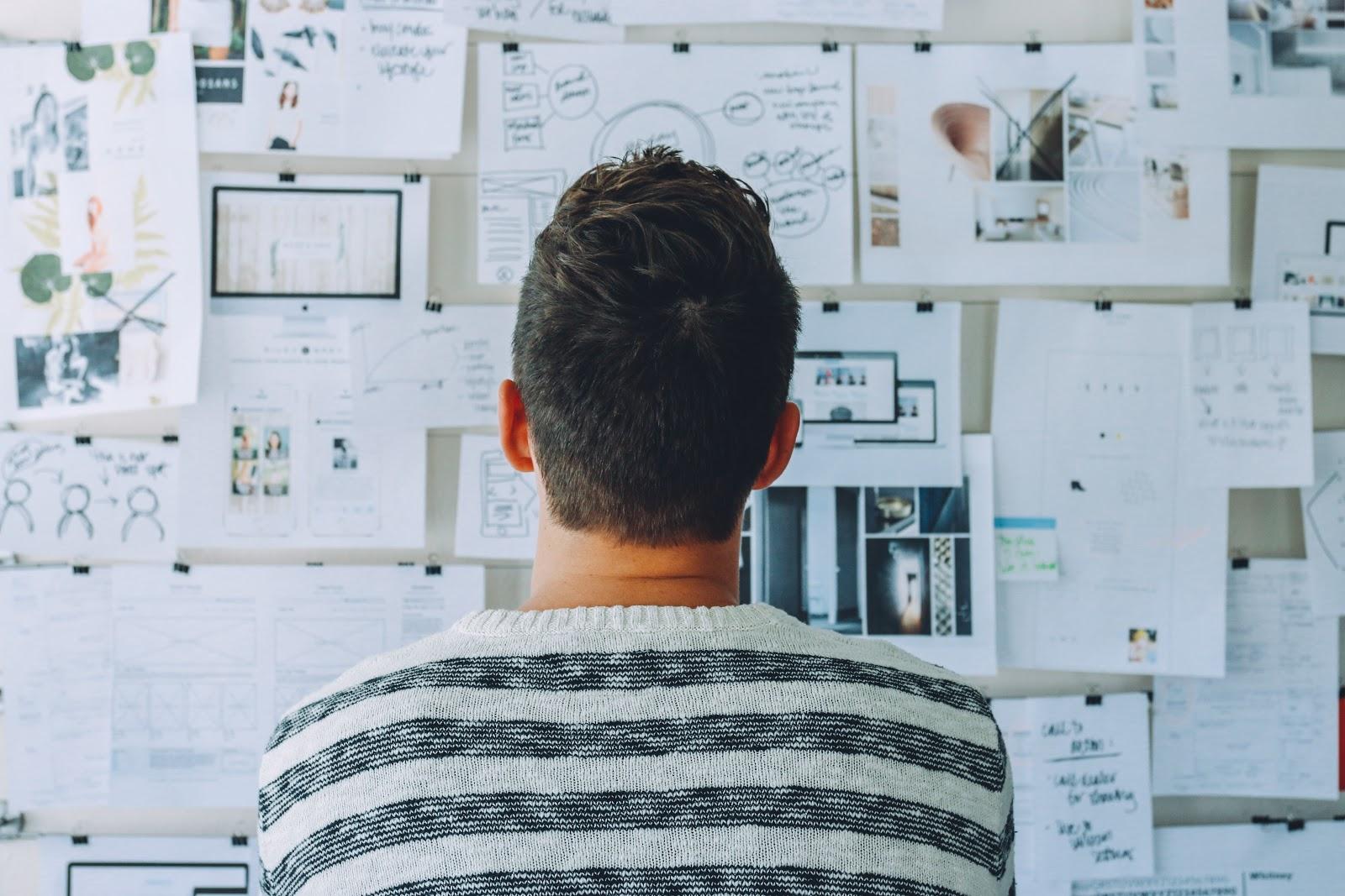 Um homem observando uma parede com anotações em papeis.