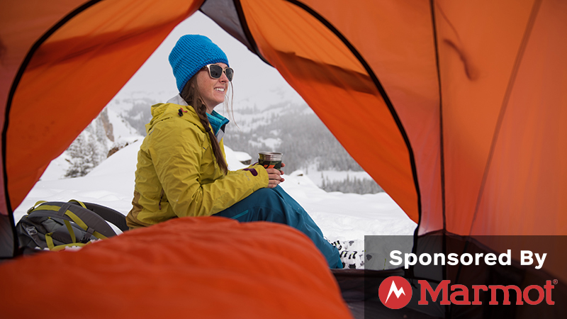 Lady in a tent, camping in the snow.