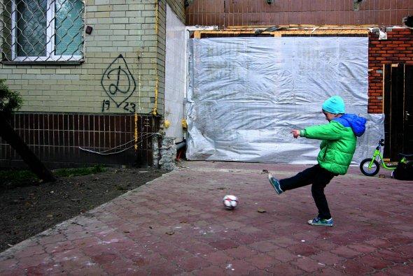 """Хлопчик грає уфутбол наОболонській набережній уКиєві. Тут настіні будинку фанати московського """"Динамо"""" залишили графіті земблемою свого клубу"""